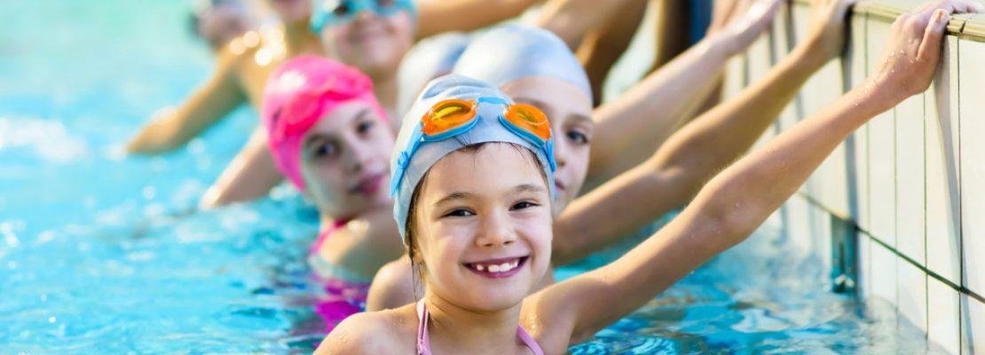 kinder-am-beckenrand-im-schwimmbecken-machen-ihr-seepferdchen